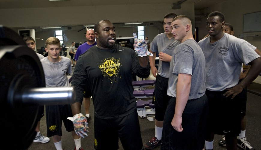 MMA head coach Buster Davis talks to his team in the weight room. Rich Cooley/Daily